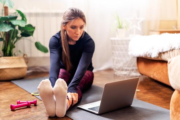 Женщина упражнениями йоги с ноутбуком дома