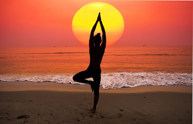 Woman practicing yoga with the sun behind her