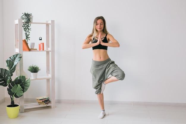 Выполняет практику йоги женщины. поза дерева стоит внутри уютной комнаты с растениями и зеленью. концепция здорового образа жизни и осознанности