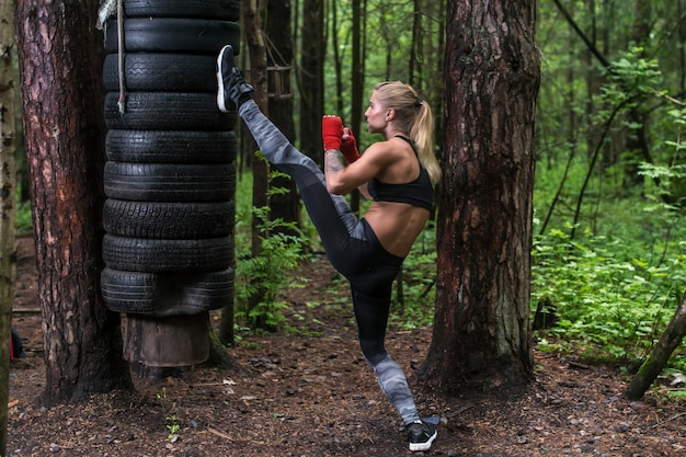 Woman practising kickboxing performing a leg axe kick working out outdoors