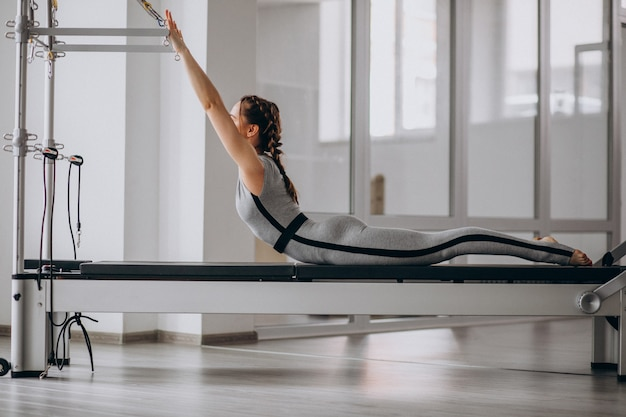 Woman practising pilates in a pilates reformer