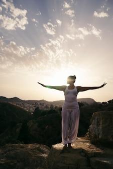 Donna che pratica yoga in campagna
