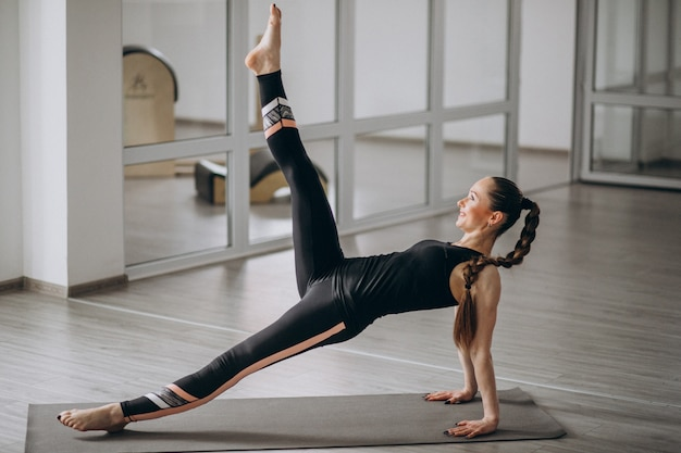 매트에 체육관에서 요가 연습하는 여자