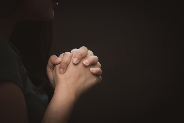 기도하고 하나님을 경배하는 여자 종교적 믿음으로기도하기 위해 손을 사용함