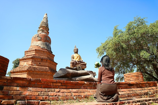Woman praying in front of buddha image at wat phra ngam temple ruins in thailand