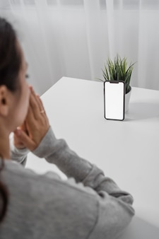 Woman praying in front of smartphone at home