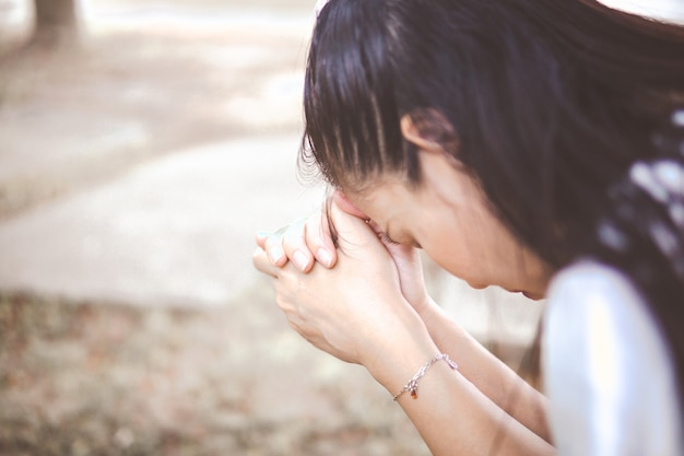 Woman praying to god at the garden in the morning.