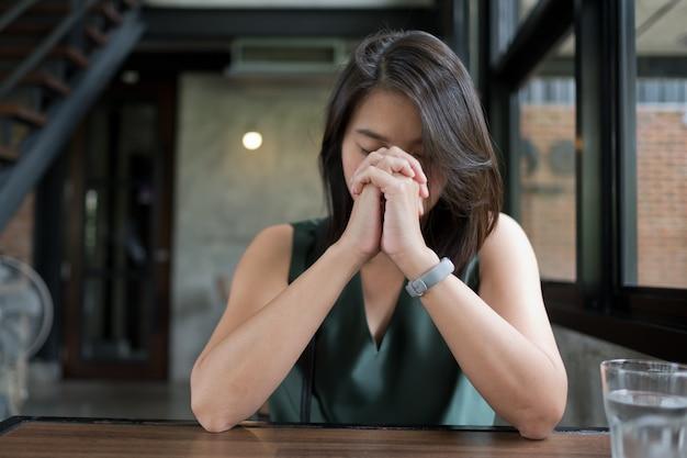Женщина молится, сложив руки в молитве