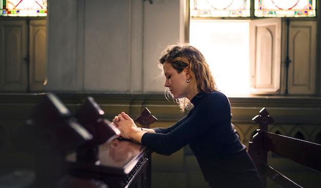 Женщина молится в церкви