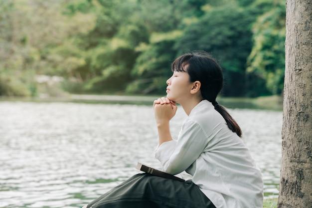朝は自然の背景に祈る女性。信仰、霊性、宗教の教会概念の聖書に祈りで折り畳まれた手