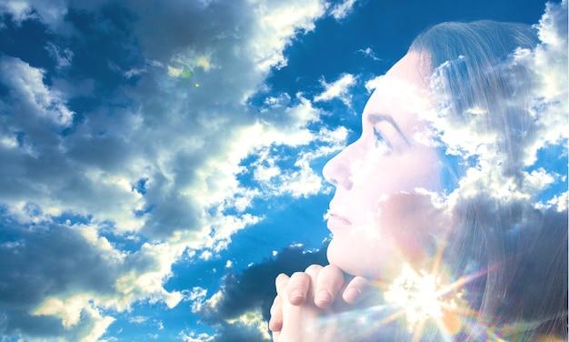 光線で青い空を祈る女性