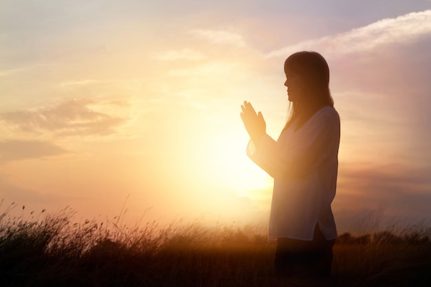 Woman praying and practicing meditating on nature sunset background, hope concept