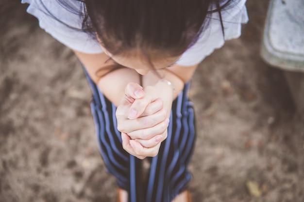午前中に庭で神に祈る女性。