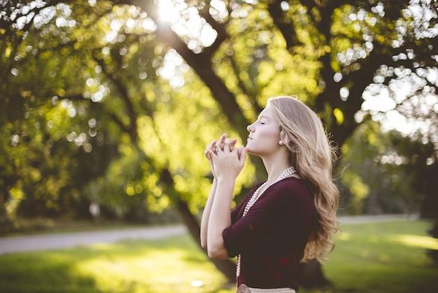 Donna che prega sotto agli alberi durante il giorno