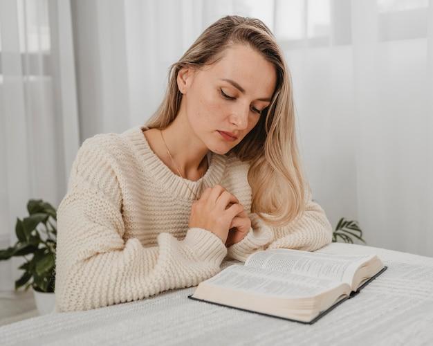 家で聖書を祈る女性