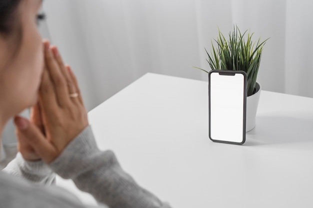 Женщина молится со смартфоном дома