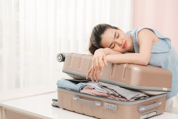 Woman prepare travel suitcase at home. excited woman trying to close full suitcase.