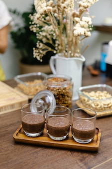 A woman prepares chia pudding in the kitchen, laying out the bottom layer of almond milk, cocoa and chia seeds.