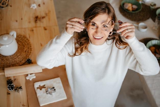 Женщина готовит рождественское печенье из теста, используя металлические формы для имбирных пряников. концепция выпечки в домашних условиях.