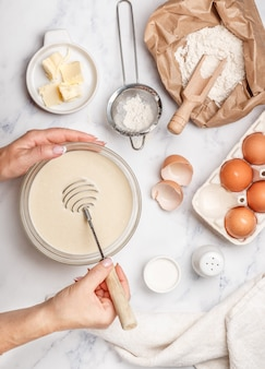 Woman prepares dough for homemade pancakes for breakfast, whisk for whipping in hands