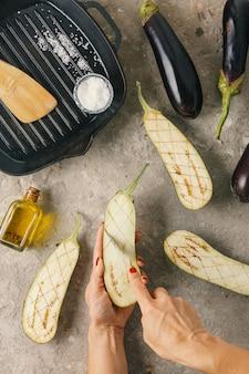 女性はビーガンの詰め物と松の実でナスを準備します Premium写真