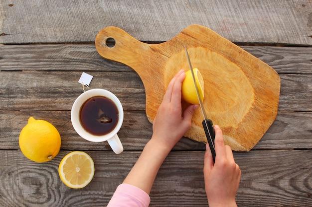 Woman prepares tea with lemon. top view.