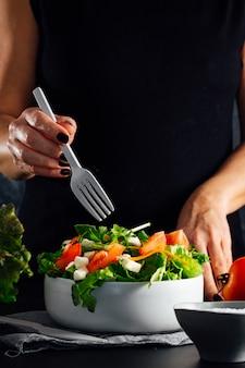 Женщина готовит салат с помидорами, салатом, оливковым маслом и солью концепция здорового питания