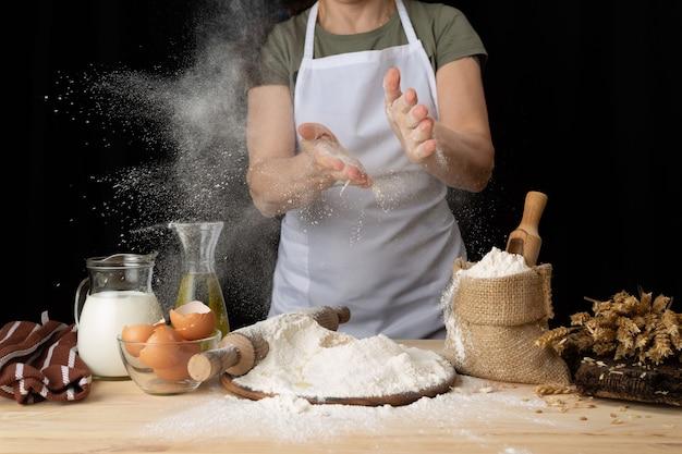 近くのパン屋の木製のテーブルでパン生地を準備する女性