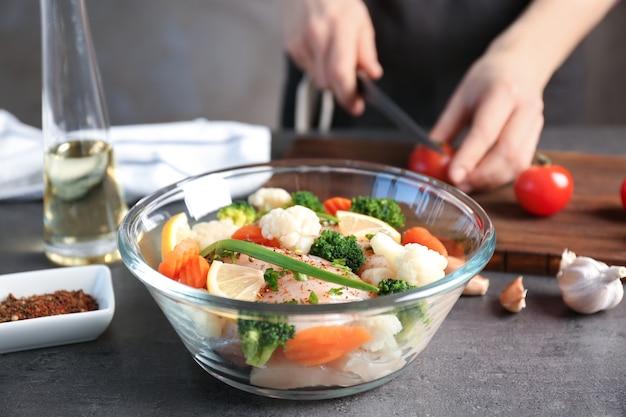 유리 그릇에 야채와 함께 닭고기를 준비하는 여자