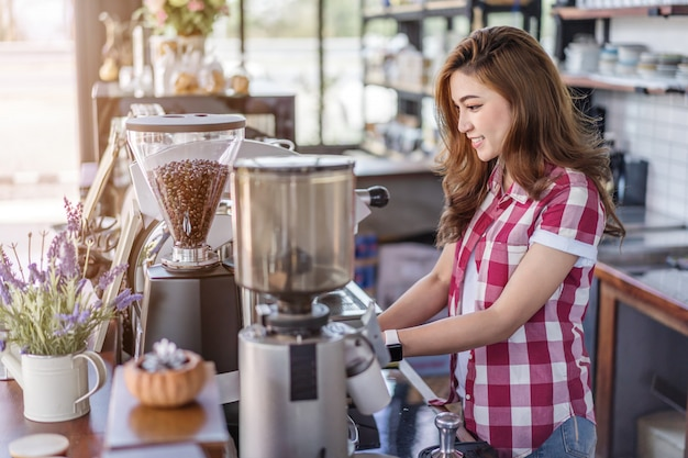 Woman preparing coffee with machine in cafe
