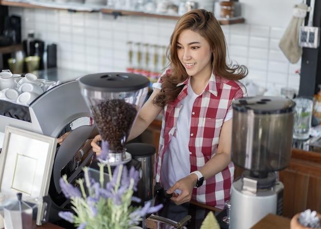 カフェでのマシンでコーヒーを準備する女性