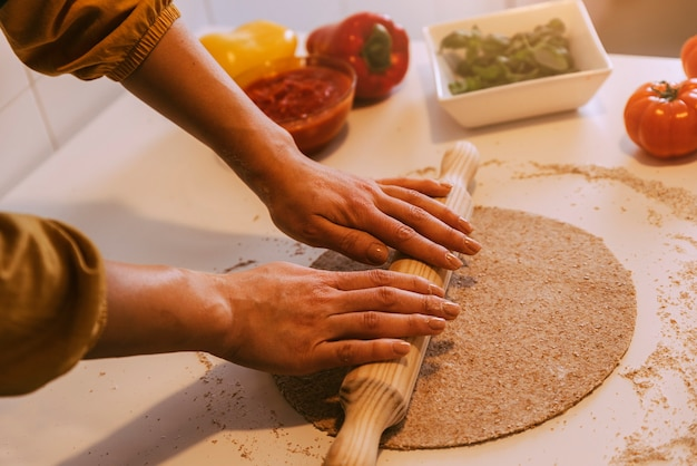 ヘルシーな食材でおいしいピザを作る女性。自家製のコンセプト。