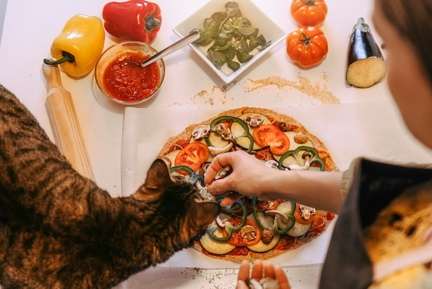 Woman preparing delicious pizza with her sweet cat. home made concept.