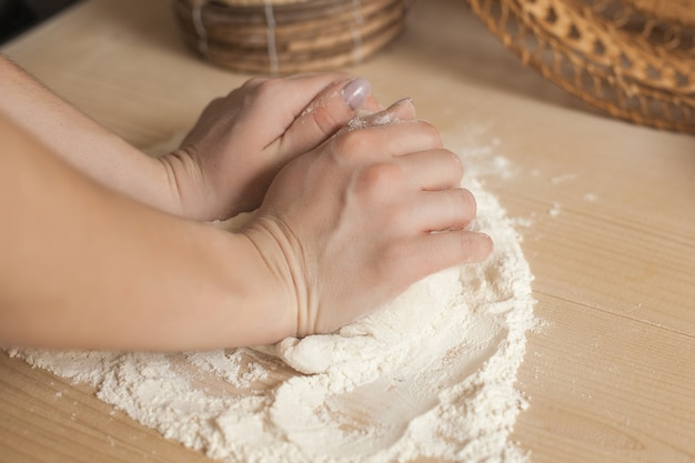 Woman preparing the dough. closeup still of woman`s hands with daugh and flour. italian food preparing process.