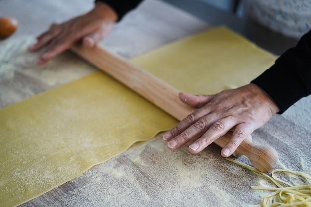 パスタ工場内でタリアテッレの生地を準備している女性
