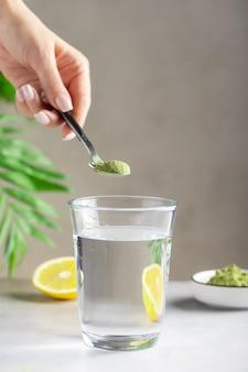 緑のスーパーフードの粉で飲み物を準備する女性