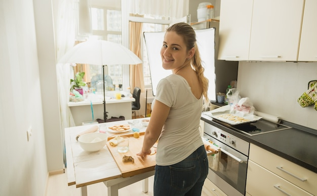 料理ブログの料理を準備している女性。キッチンの写真機材