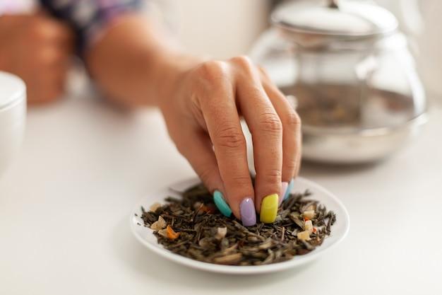 朝食のキッチンでarmoaticハーブを使用して緑茶を準備する女性