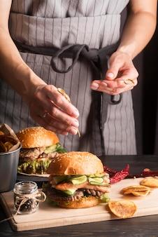 Женщина готовит гамбургеры и картофель фри