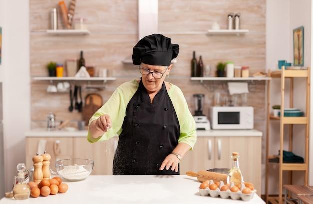 Женщина готовит домашнее печенье, выкладывая стол муки на домашней кухне