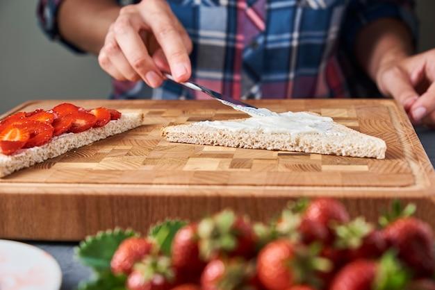 Женщина готовит тосты бутерброды со свежими ягодами на кухне