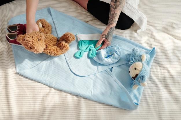 Женщина готовит пеленки, игрушки и шапочки для новорожденного