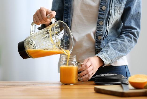 Женщина готовит вкусный смузи на кухне