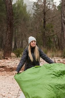 Woman preparing tent for camping
