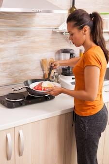 卵、ベーコン、トマトを使って食事を準備する女性。