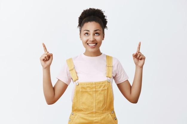 ステージに上がる準備をしている女性が、神の指示を与えて彼女を助けます。黄色のオーバーオールの黒い肌、人差し指で見上げて上向き、空を見つめる魅力的な幸せでのんきな若い女性
