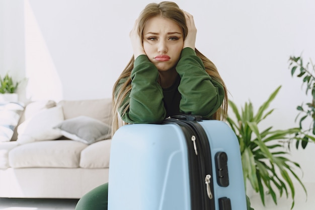 自宅で旅行スーツケースを準備する女性