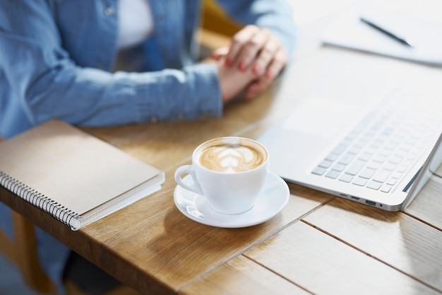 Woman preparing for work in cafe with laptop