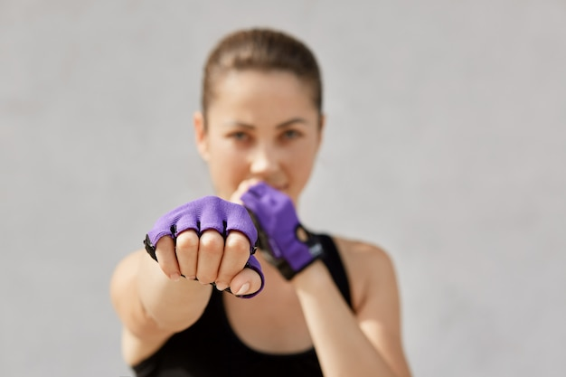 Woman preparing for workout at sport studio. female in sportswear and fitness gloves standing isolated on gray