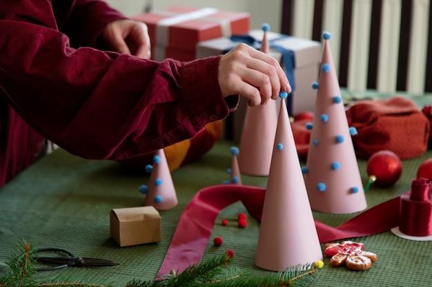 집에서 생태학적으로 종이 크리스마스 트리를 준비하는 여자